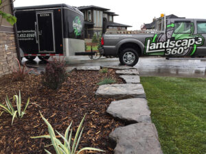 Stone-edge-garden-bed-with-truck-in-background